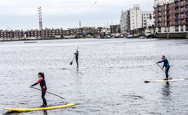 Three people stand up paddle boarding in Dublin