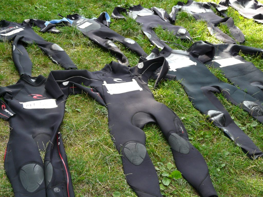 Nine wet suits in different sizes lying flat on grass